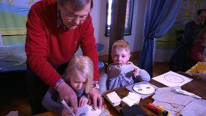Ukki Pertti Paajanen askartelee viisivuotiaiden kaksosten Mannan ja Nooan kanssa norppanaamareita.