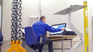Insinööri ohjaa tietokoneen avulla mittalaitetta.