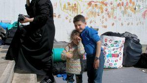 Lapset jättävät kädenjälkiään muistoksi Pireuksen sataman hätäleirin seinään.