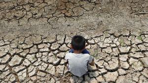 Poika istui halkeilleella maalla kuivuneen kastelukanavan äärellä Chachoengsaon provinssissa Thaimaassa lauantaina 5. maaliskuuta.