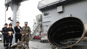Eteläkorealaiset sotilasviranomaiset tutkivat sotilasaluksella merestä nostettua esinettä.