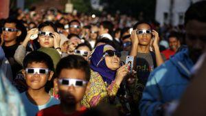 Ihmisiä auringonpimennyksen aikaan Indonesian pääkaupungissa Jakartassa.