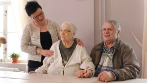 Senioripäiväkoti Varpusen yrittäjä Mari Kotilainen asiakkaansa Anjan ja hänen omaishoitajansa Simo Angelin kanssa.