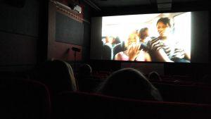 Ihmiset katsovat teatterissa Hanna Karppisen Oma maa mansikka -elokuvaa