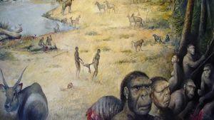 Piirroskuvassa esi-ihmisiä ja eläimiä, muun muassa kirahveja ja antilooppeja, joen varressa.