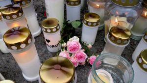 Hautakynttilöitä ja ruusuja betonisillalla