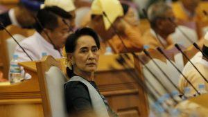 Aung San Suu Kyi istuu kansanedustajien joukossa.