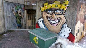 Taitelija Henden graffititeos, jossa hymyilevä kuningas ja maalari-Robin Hood