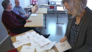 Eläkevalmentaja levittää pöydälle kortteja, joissa on lauseita
