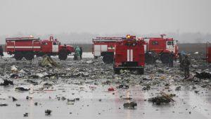 Useita lentokentän paloautoja ja romua maassa.