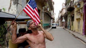 Kuubalainen mies suutelee Yhdysvaltain lippua Havannassa.