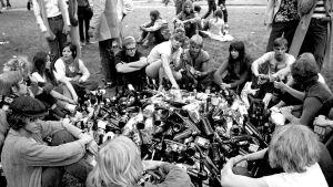 nuoria puistossa juomassa, keskellä iso kasa pulloja