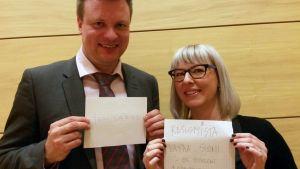 Ville Skinnari pitää kylttiä, jossa lukee ihmisarvo ja Aino-Kaisa Pekonen pitää kylttiä, jossa lukee rasismista vapaa Suomi on toiveeni