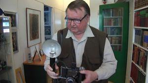 Lehtikuvaaja Antti Suominen tarkastelee vanhaa kameraa.