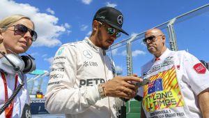 Mercedeksen Lewis Hamilton näprää kännykkäänsä