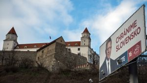 """Puoluejohtaja Rober Ficon kuva ja """"Puolustamme Slovakiaa"""" -teksti julisteessa Bratislavan linnan edessä."""