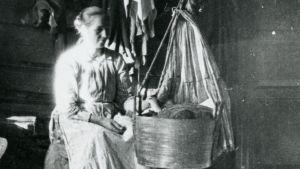 Nainen istuu kehdon äärellä. Valokuva on noin sata vuotta vanha.
