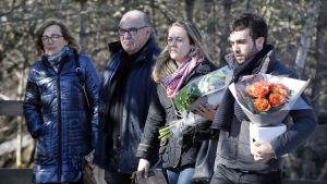 Nelihenkinen perhe kantaa kukkia.