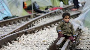 Pieni lapsi istuu ratakiskolla, taustalla telttaleiri.