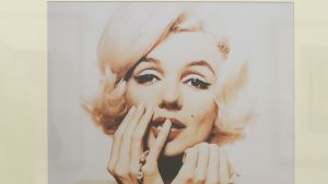 Marilyn Monroe nojaa muotokuvassa poskeensa, toisen käden pikkusormi huulillaan.