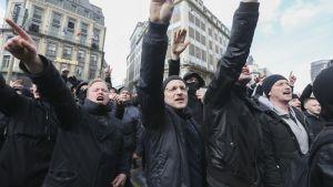 Mustaan pukeutuneita miehiä kädet pystyssä natsitervehdyksessä.