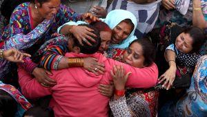Itkeviä naisia toisiinsa takertuneina.