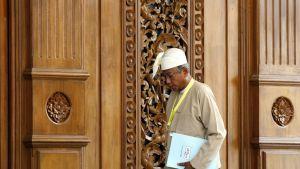 Htin Kyaw suuren, koristeellisen oven edessä.
