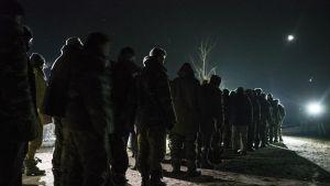 Joukko sotilaita odottaa yön pimeydessä. Ukrainalaiset sotavangit odottavat vankien vaihtoa Funzen kaupungissa Itä-Ukrainassa helmikuussa 2015.