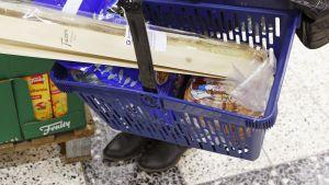 Nainen kantaa ruokakoria kaupassa.