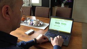 Mies seuraa tietokoneeltaan talonsa sähkönkulutusta
