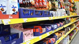 Kuvassa kaupan karkkihylly, jossa näkyy suklaata ja karkkipusseja.