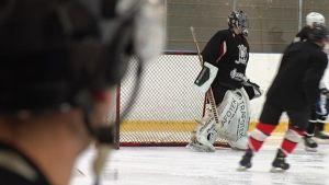 Vaihtoaitiossa seisova mies seuraa joukkueensa harjoituksia jääkiekkokaukalossa.