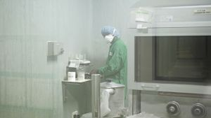 Mies lääketehtaan laitteen ääressä.