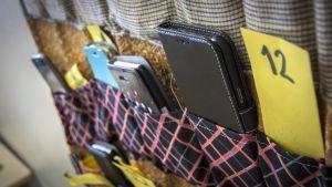 Kännykättömän oppitunnin kännykkäpussi luokkahuoneen seinällä.