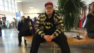 nuori mies istuu linja-autoaseman odotushuoneessa