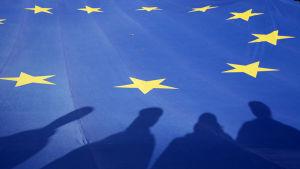 suuren eu-lipun päälle lankeaa ihmisten varjoja.