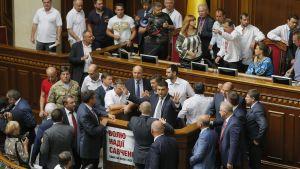 Ihmiset ympäröivät puhemies Volodymyr Hroismania Ukrainan parlamentissa.