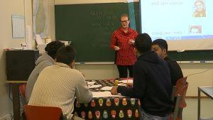 Turvapaikanhakijoita istuu pöydän ääressä koululuokassa ja opettaja seisoo heidän edessään.