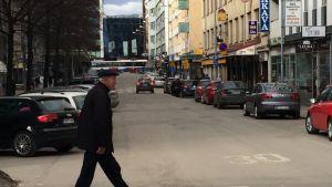 Mies kävelee Tuomiokirkonkadun poikki.