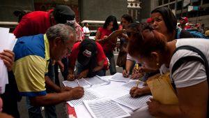 Joukko ihmisiä allekirjoittaa papereita pöydän ääressä.