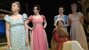 Äiti ja neljä tytärtä teatterinäytelmässä lavalla.