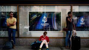 Al-Jazeeran mainoskylttejä, kolme ihmistä edessä.