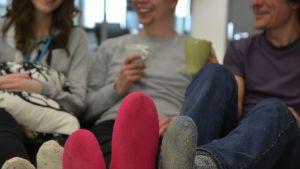 Kolme henkilö istumassa sohvalla, villasukat pöydällä