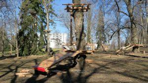 Seikkailupuiston rakenteita puissa, taustalla hotelli