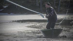 Mies hinaa itseään salmen yli veneessä.