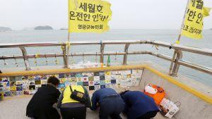 Omaisia kunnioittamassa uhrien muistoa Jindon satamassa.