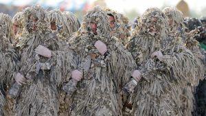 naamiointiasuihin sonnustautuneita sotilaita