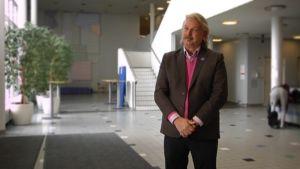 Colin Allen seisomassa Valkean talon aulassa.
