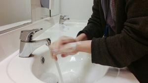 Henkilö pesee käsiään lavuaarissa.
