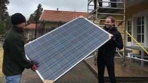miehet kantavat aurinkopaneelia